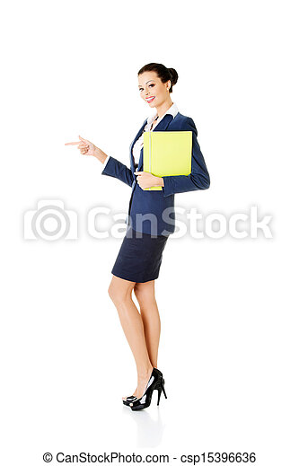 Happy young success business woman pointing on copy space - csp15396636