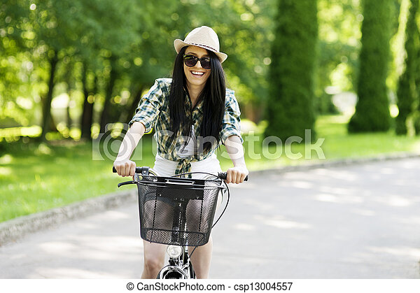 Happy young woman cycling through the park - csp13004557