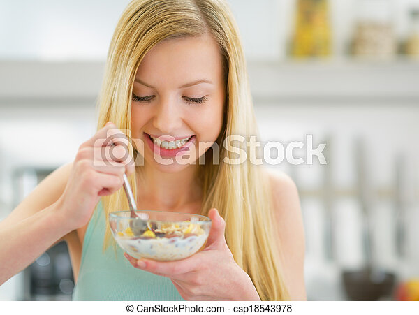 Happy young woman eating muesli in kitchen - csp18543978