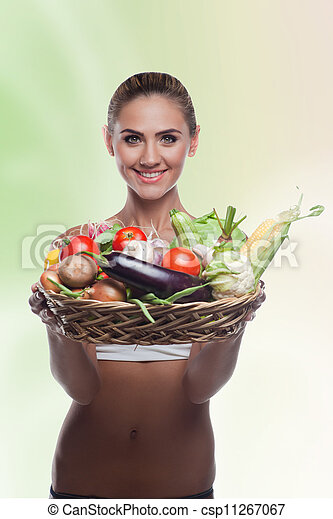 Happy young woman holding basket with vegetable. Concept vegetarian dieting - healthy food - csp11267067