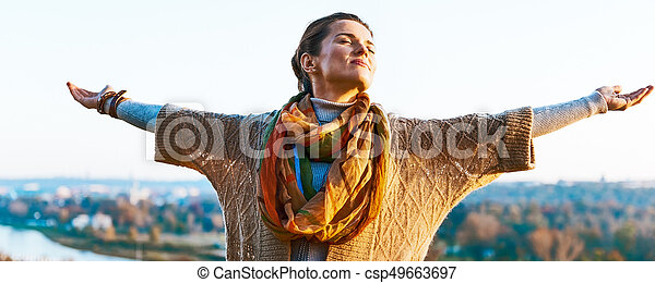 Happy young woman in autumn outdoors in evening rejoicing - csp49663697