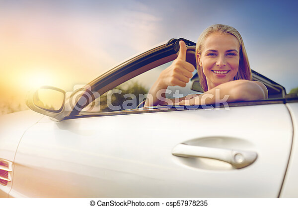 1a7cf5c6c happy young woman in convertible car thumbs up