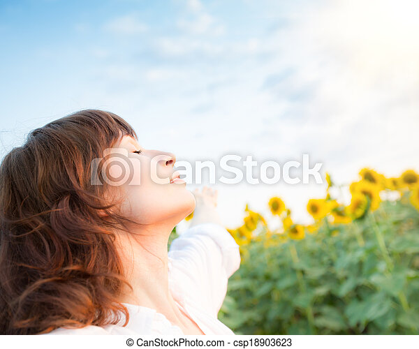 Happy young woman in sunflower spring field - csp18903623