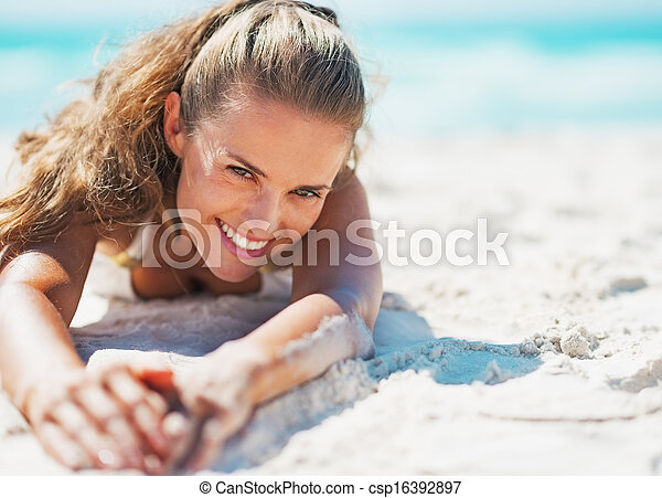 Happy young woman in swimsuit relaxing on beach - csp16392897