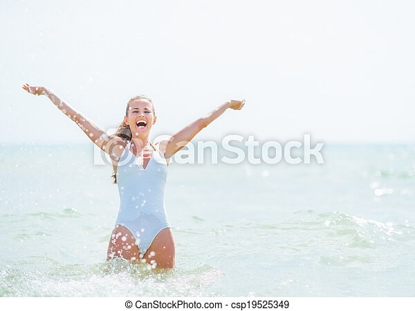 Happy young woman in swimsuit standing in sea and rejoicing - csp19525349