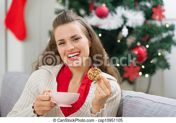 Happy young woman near Christmas tree with cup and cookie - csp10951105