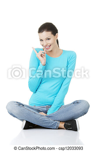 Happy young woman pointing on copy space. - csp12033093