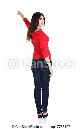 Happy young woman pointing on copy space - csp17788107