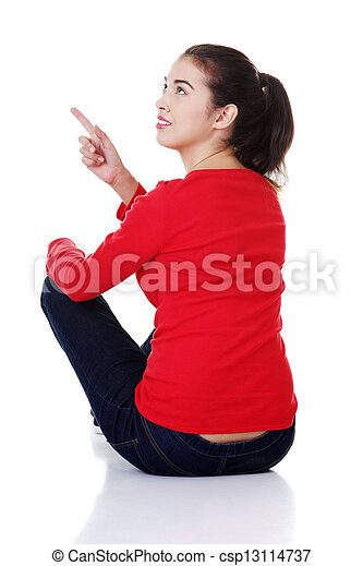 Happy young woman pointing on copy space. - csp13114737