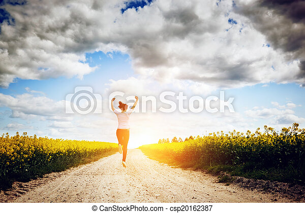 Happy young woman running and jumping for joy towards sun - csp20162387