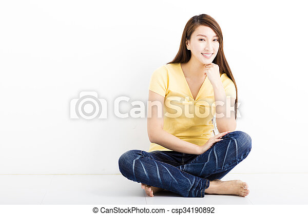 happy young woman sitting on the floor - csp34190892