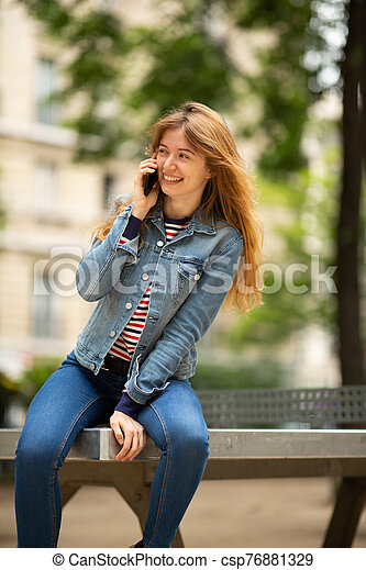 happy young woman sitting outside in park talking with cellphone - csp76881329