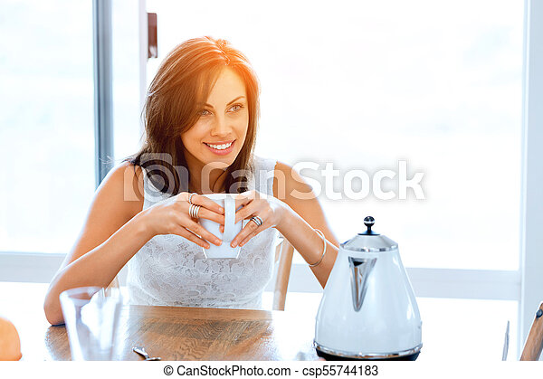 Happy young woman with cup of tea or coffee at home - csp55744183