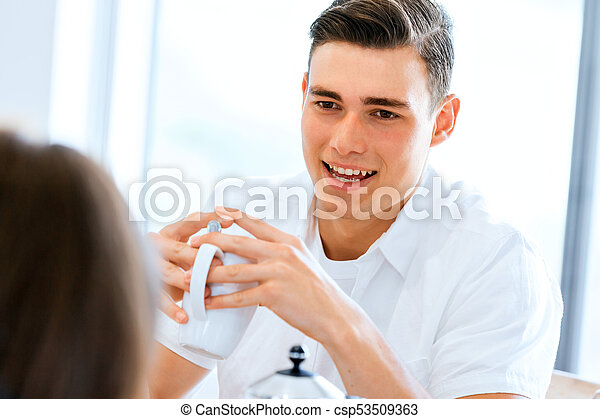 Happy young woman with cup of tea or coffee at home - csp53509363