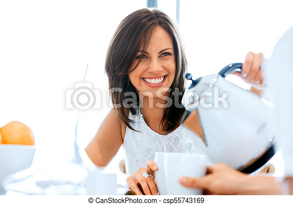 Happy young woman with cup of tea or coffee at home - csp55743169