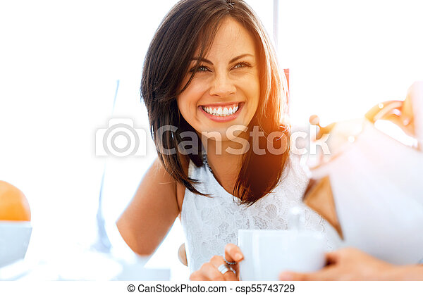 Happy young woman with cup of tea or coffee at home - csp55743729