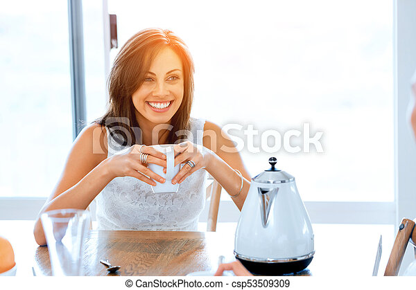 Happy young woman with cup of tea or coffee at home - csp53509309