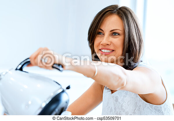 Happy young woman with cup of tea or coffee at home - csp53509701
