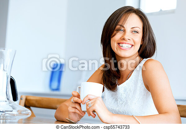 Happy young woman with cup of tea or coffee at home - csp55743733