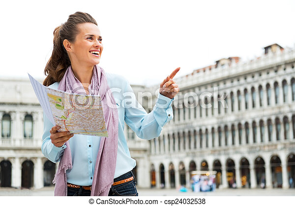 Happy young woman with map pointing on piazza san marco in venic - csp24032538