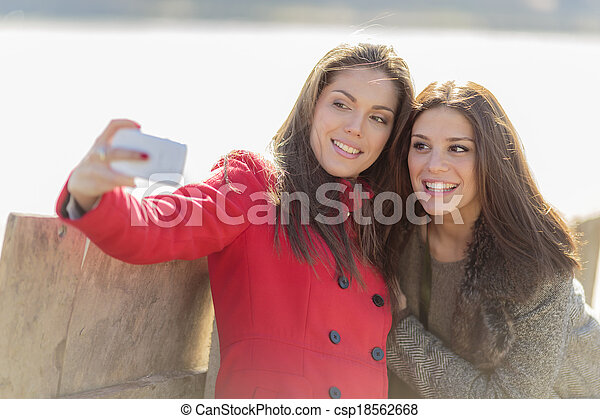 Happy young women taking photo with mobile phone - csp18562668