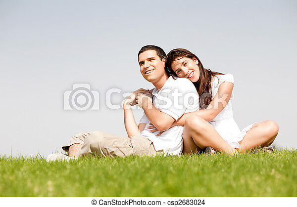 Happy young women with arms around her husband and laying on his shoulder in a park - csp2683024