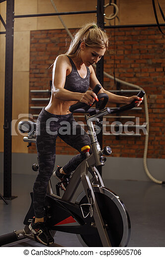 hardworking young beautiful woman doing exercise on bicycle training apparatus - csp59605706