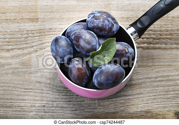 harvest of ripe plums on the table - csp74244487