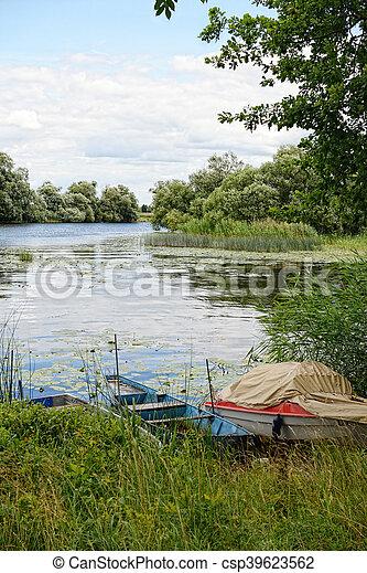 Havel river at summer time (Brandenburg, Germany). boats on shore - csp39623562