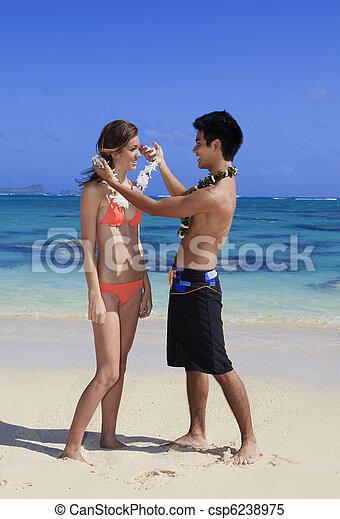 hawaiian man puts a lei on a young woman - csp6238975
