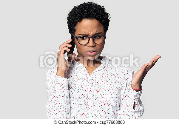 Head shot annoyed African American woman talking on phone - csp77683808