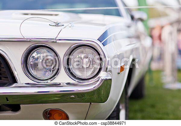 Headlights Of Old White American Muscle Car With Chrome Bumper