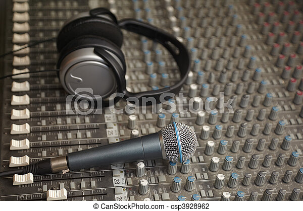headphones and microphone on old dirty sound mixer pult. microphone in focus - csp3928962