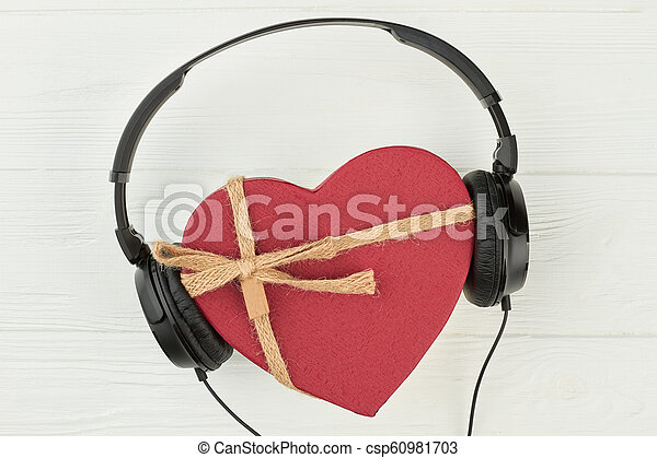 Headphones with red heart-shaped gift box. black headset and gift box in a shape of heart over white background. musical gift concept. & Headphones with red heart-shaped gift box. black headset and gift ...