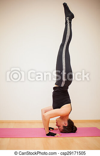 headstand in a yoga studio profile view of a tall and