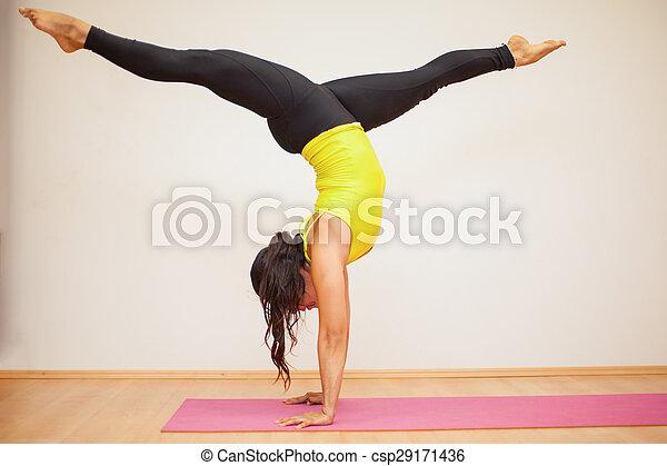 headstand leg split in a yoga studio profile view of a