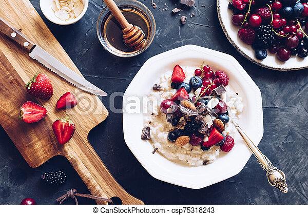 Healthy breakfast oatmeal porrige with berries - csp75318243