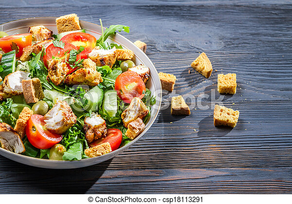 Healthy Caesar salad made of fresh vegetables on blue table - csp18113291