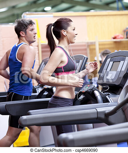 Healthy couple running on a treadmill in a sport centre - csp4669090