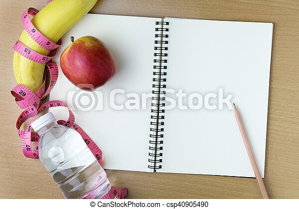 Healthy eating concept, tape measure, fruit and water bottle on a wooden background, blank copy space notebook - csp40905490