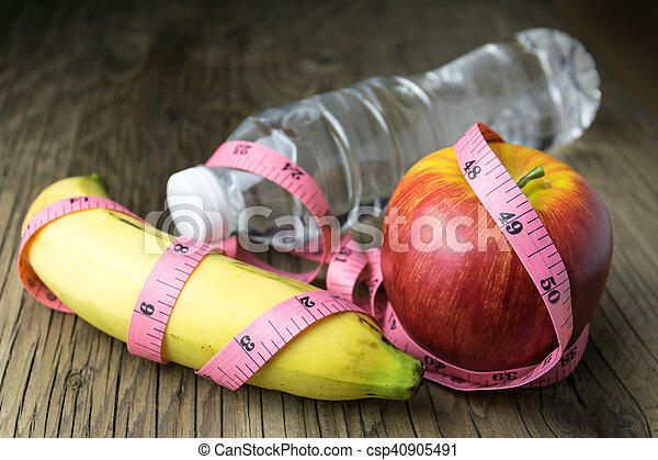 Healthy eating concept, tape measure, fruit and water bottle on a wooden background - csp40905491