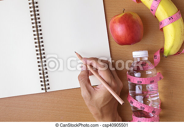Healthy eating concept, tape measure, fruit and water bottle on a wooden background, blank copy space notebook - csp40905501