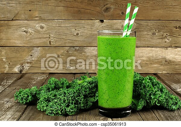 Healthy green smoothie with kale in a glass against a rustic wood background - csp35061913