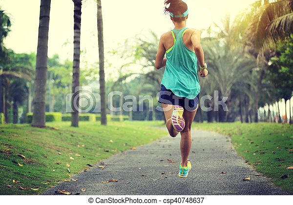 healthy lifestyle young sporty asian woman running at tropical park - csp40748637