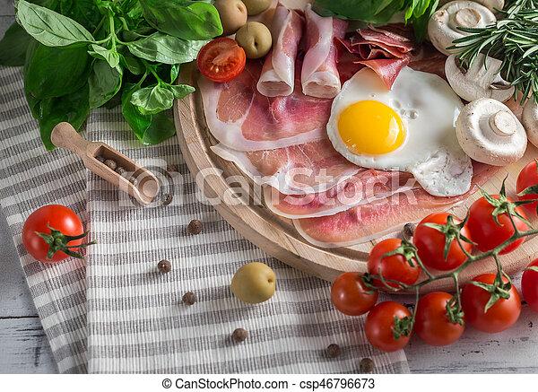 Healthy Mediterranean breakfast ingredients, ham, fried eggs, tomatoes