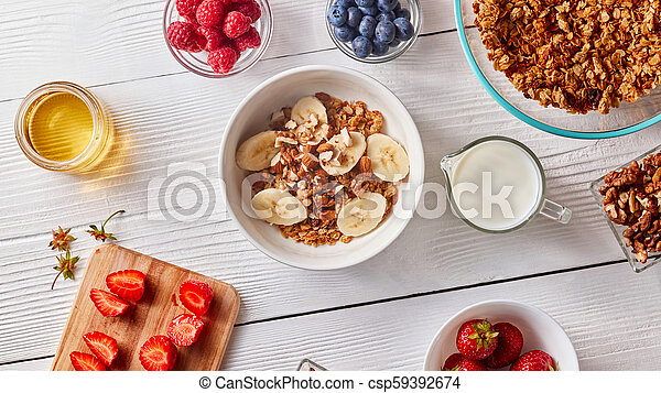 Healthy natural breakfast with organic ingredients corn flakes, banana slices in white bowl and milk, berries, honey, nuts on white. - csp59392674