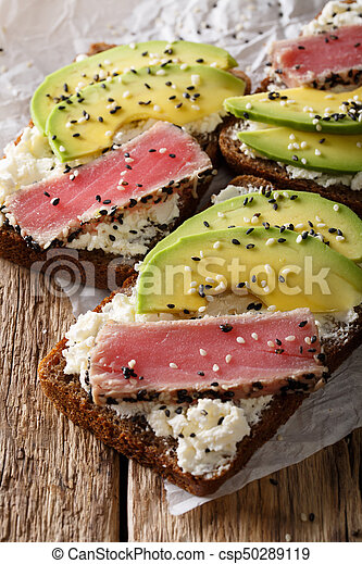 Healthy open sandwiches with fried tuna in sesame, avocado and cream cheese close-up. vertical - csp50289119
