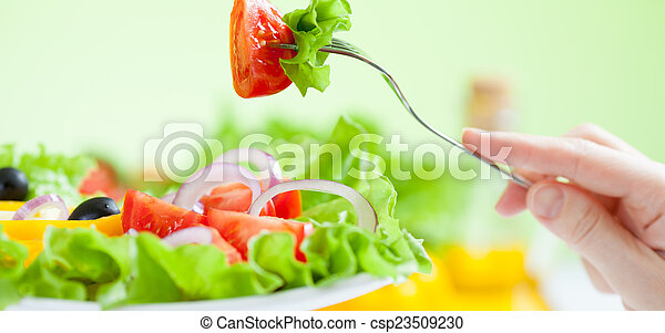 healthy salad eating with vegetables on green background - csp23509230