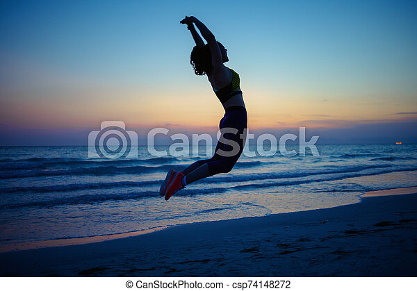 healthy woman on ocean shore in evening doing hiit workout
