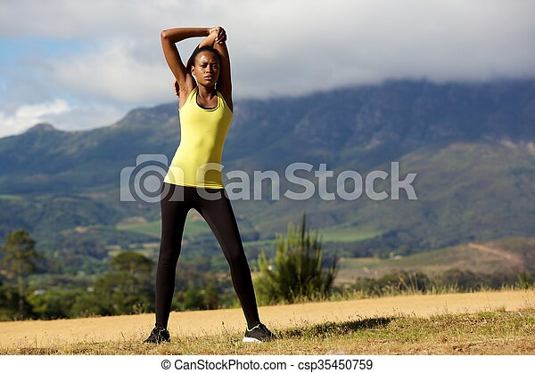Healthy young woman doing stretching exercise - csp35450759